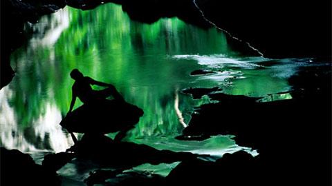 Một hồ nước ở Rio Frio Cave, phản chiếu hình ảnh cây cỏ của rừng Belize's Chiquibul và bóng của một người khách du lịch. Nơi đây là một điểm đến rất thu hút khách du lịch.