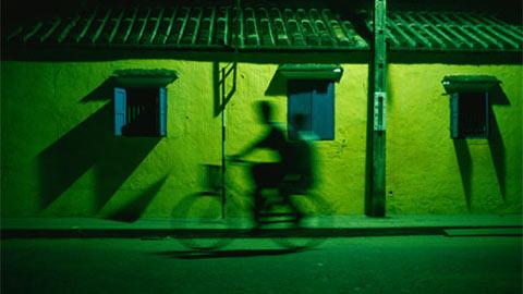 Hai đứa trẻ đang dạo đêm trên xe đạp tại phố cổ Hội An, Việt Nam. Một màu xanh thanh bình. Hội An là Di sản Thế giới với nhiều công trình lịch sử từ thế kỷ 15 đến 19
